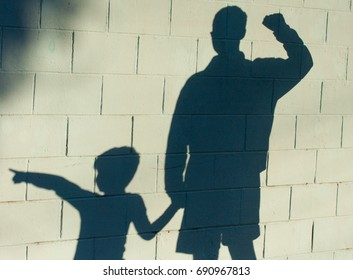 Father and son shadow on wall holding hands