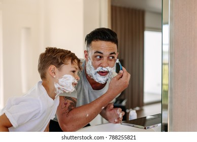 Father and son shaving together at home bathroom. Young man and little boy with shaving foam on their faces are shaving and looking into the mirror.