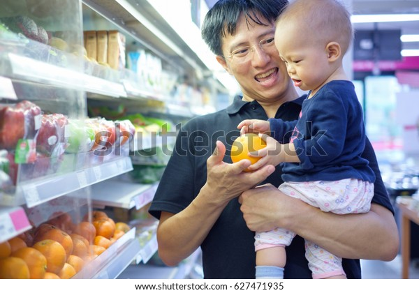 Father and son are shopping in a supermarket. Smiling Dad and Cute little Asian 12 months / 1 year old baby boy child choosing fruits in grocery store, Kid first experience concept