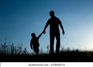 father and son silhouette on sunset