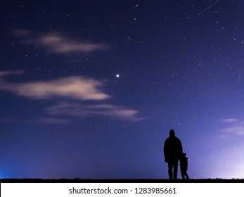 Father and Son silhouettes against the Background of Blue Night