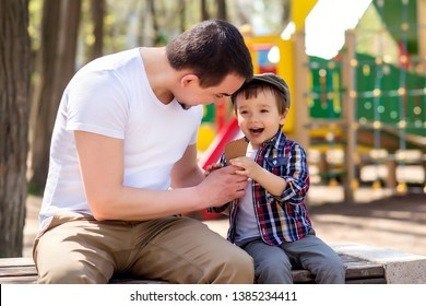 Father and son sit on bench and eat ice cream in park in sunny spring or summer day. Both dad and child are smiling, playground in background. Family fun outdoor and father and son spend time together