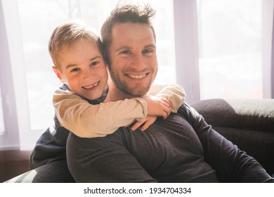 A father and son sit on the sofa at home