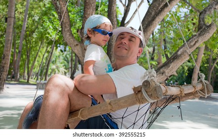 Father and son sits on an hammock in Maldive Island