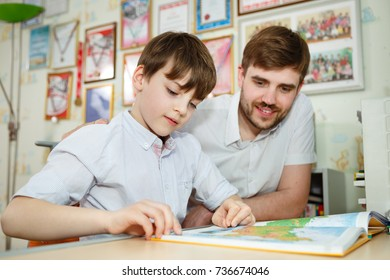 Father and son sitting at desk, and looking at geography maps on background child room. Adult man helping child to study concept