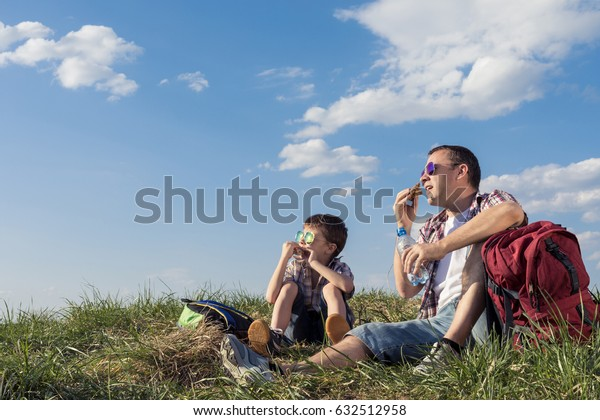 Father and son sitting in the field at the day time. People having fun outdoors. Concept of friendly family.