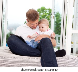 Father and son sitting in front of window using a digital tablet