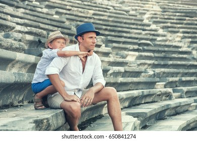 Father with son sitting on antique amfitheater steps. Side, Turkey