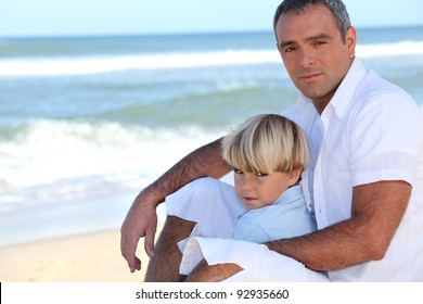 Father and son sitting on a beach