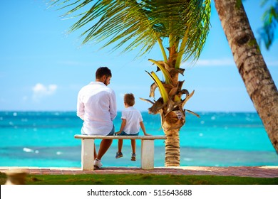 father and son sitting on bench in front of the ocean