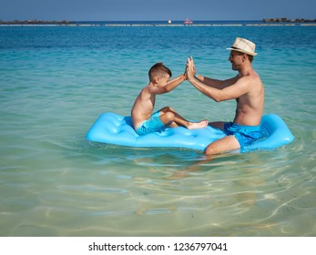 Father and son are sitting on a blue floater in the crystal ocean water. They are having fun and making high five gesture.