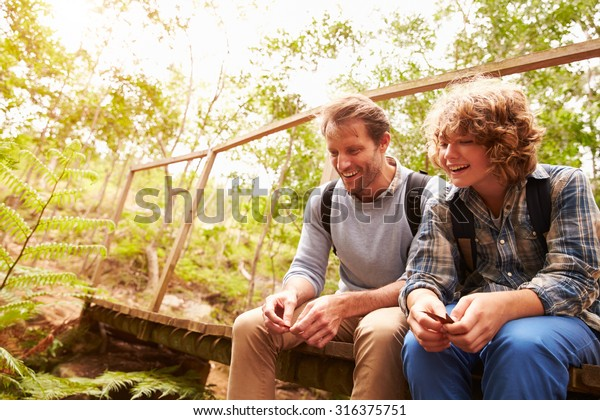 Father and son sitting on a bridge in a forest, close up