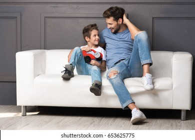 Father and son are sitting on the couch