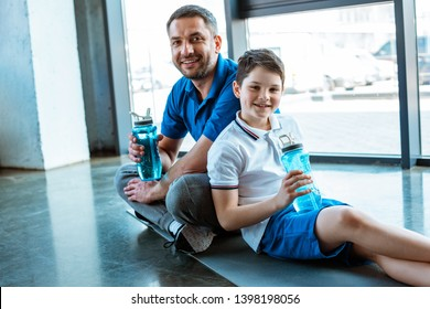 father and son sitting on fitness mat with sport bottles and looking at camera at gym