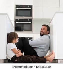 Father and son sitting on floor in kitchen and talking