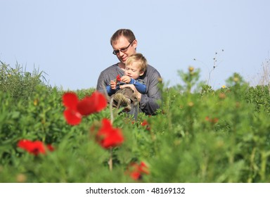 Father and son sitting on the green grass and looking at the flowers