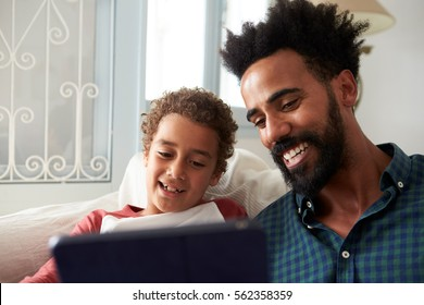 Father And Son Sitting On Sofa Using Digital Tablet