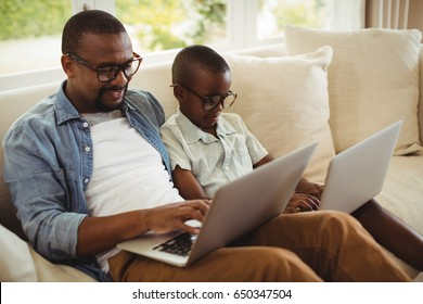 Father and son sitting on sofa and using laptop at home