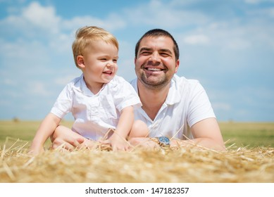 Father And Son Sitting On Straw Bales