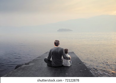 Father and son sitting on a wharf and observing the panorama