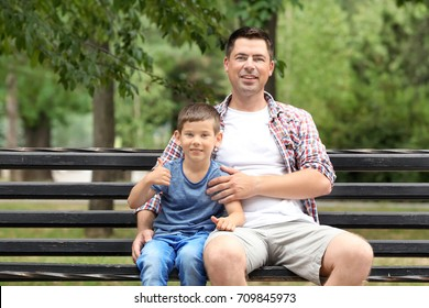 Father and son sitting on wooden bench outdoors