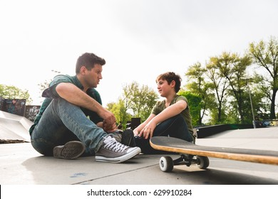 Father and Son sitting at Skate Park
