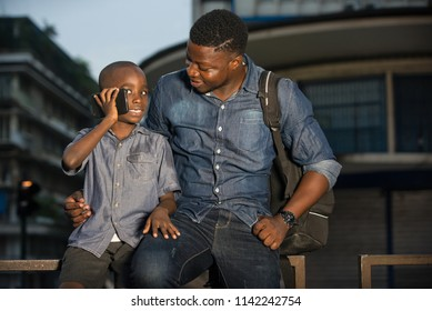 Father and son sitting in the street waiting for a car, young child talking on the cell phone beside his father. concept of tourist and travel with children.