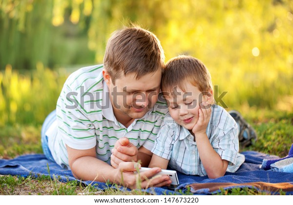 Father and son with a smartphone outdoors together