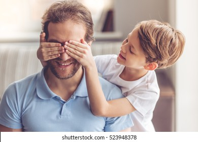 Father and son are smiling while spending time together. Little boy is covering his dad eyes