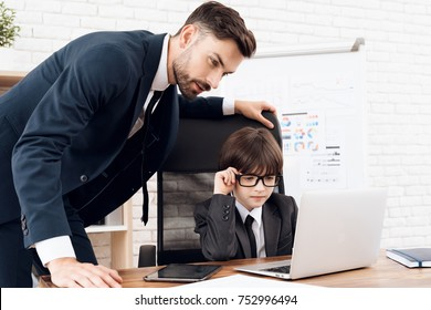 Father and son spend time together. Dad and son in the same clothes. Father teaches his son the basics of business. The son is sitting at the laptop, his father is standing next to him.