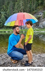 Father and son are spending fathers day in the countryside near river, dad is holding umbrella above his child to protect him from the rain.
