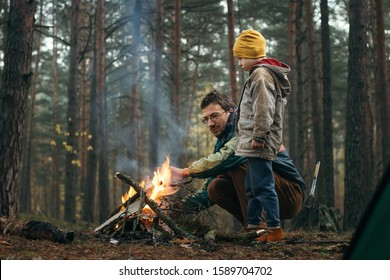 Father and son spending happy leisure time together outdoors in forest trees background. Family man child making campfire on nature woods. Relations happiness activity holidays vacation journey