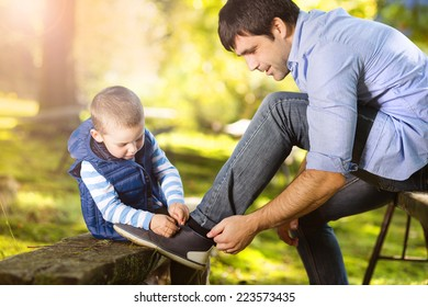 Father and son spending time together in summer nature, little boy is tying his father's shoes