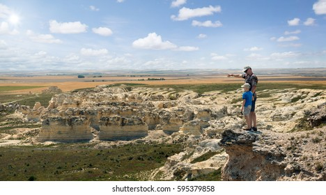 Father and son stand on the rock and look at the horizon line. Castle Rock Badlands. Western Kansas, US