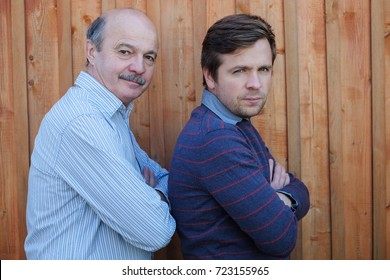 Father and son stand together near wooden background. Good family relationship between generations