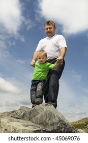 Father and Son standing at the edge of rock. Against the background sky and the clouds.