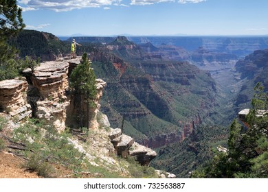 Father and son are standing on the edge of a rock in the Grand Canyon and an adult is talking to a teenager. Arizona National Park, USA