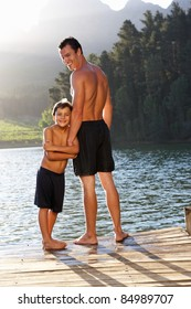 Father and son standing on jetty
