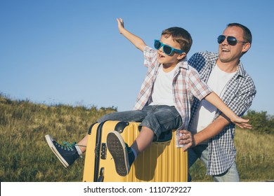 Father and son standing on the road at the day time. Concept of tourism.