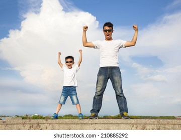 father and son standing  and raising hands