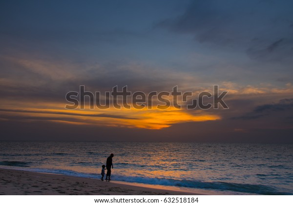Father and the son strolling in the sunset.