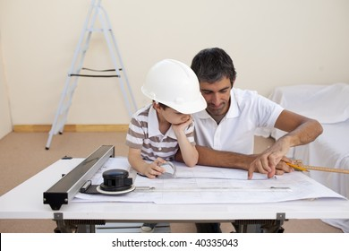 Father and son studying working with plans at home