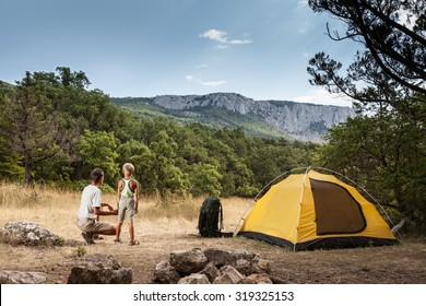 Father with son in the summer camping on a meadow