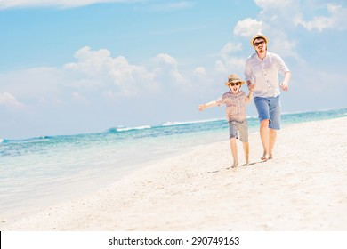 Father and son in summer nats and sunglasses running barefoot on the sea surf line having great holidays time on beautiful sunny day. Bali, Pandawa beach