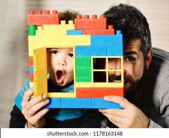 Father and son with surprised faces look through window of toy construction. Family and childhood concept. Dad and kid with hide behind building wall made of plastic blocks. Boy and man play together