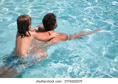 Father and son swimming in pool, summer family. Child pool party. Family leisure. Summer vacation. Father and son in pool. Child with dad playing in swimmingpool.