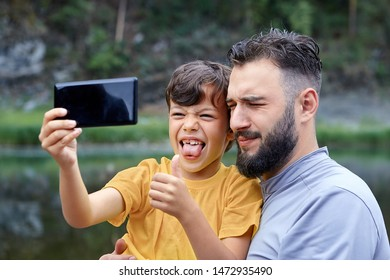 Father and son take selfies in nature, using a mobile phone camera, the boy is grimacing and showing his tongue.