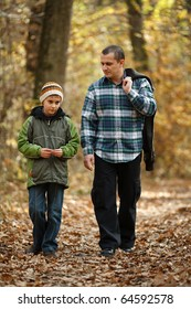Father and son talking a walk outdoor in a forest, in an autumn day