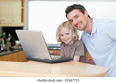 Father and son together with notebook in the kitchen