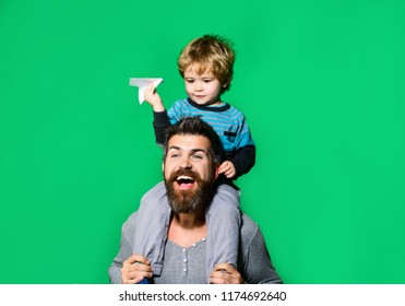 Father and son together play with paper plane. Dream, career, aspiration, adventure, education. Air mail delivery, aircraft construction.Little boy play with paper plane pretending be flying in travel
